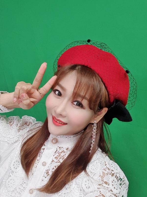 노수현 가수가 둥그런 빨간 모자를 쓰고 손으로 V자를 그려보이고 있다. (사진제공=노수현 가수)
